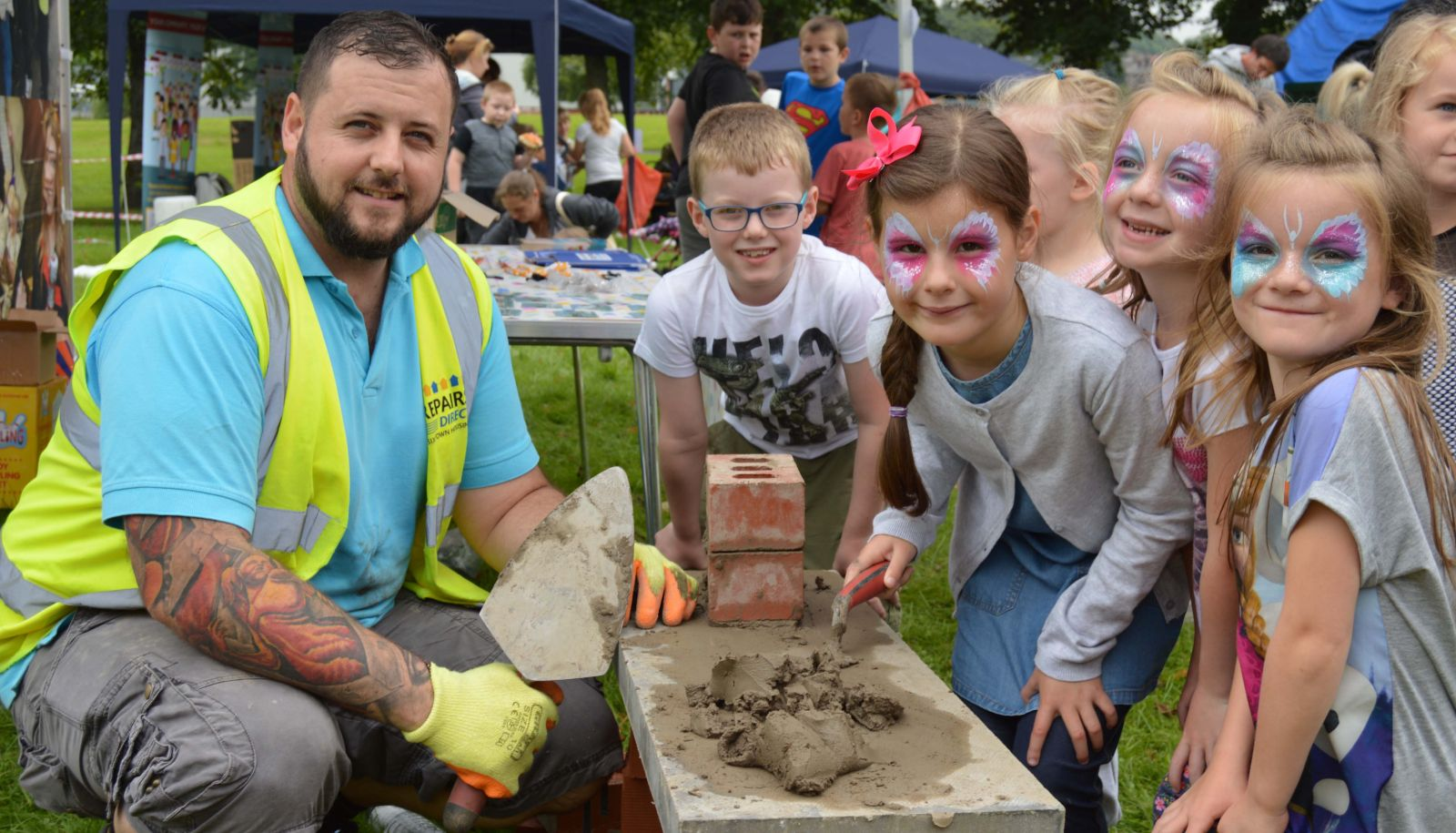 Young people get a lesson in bricklaying at Six Town Housing's Summer Roadshow in Bury