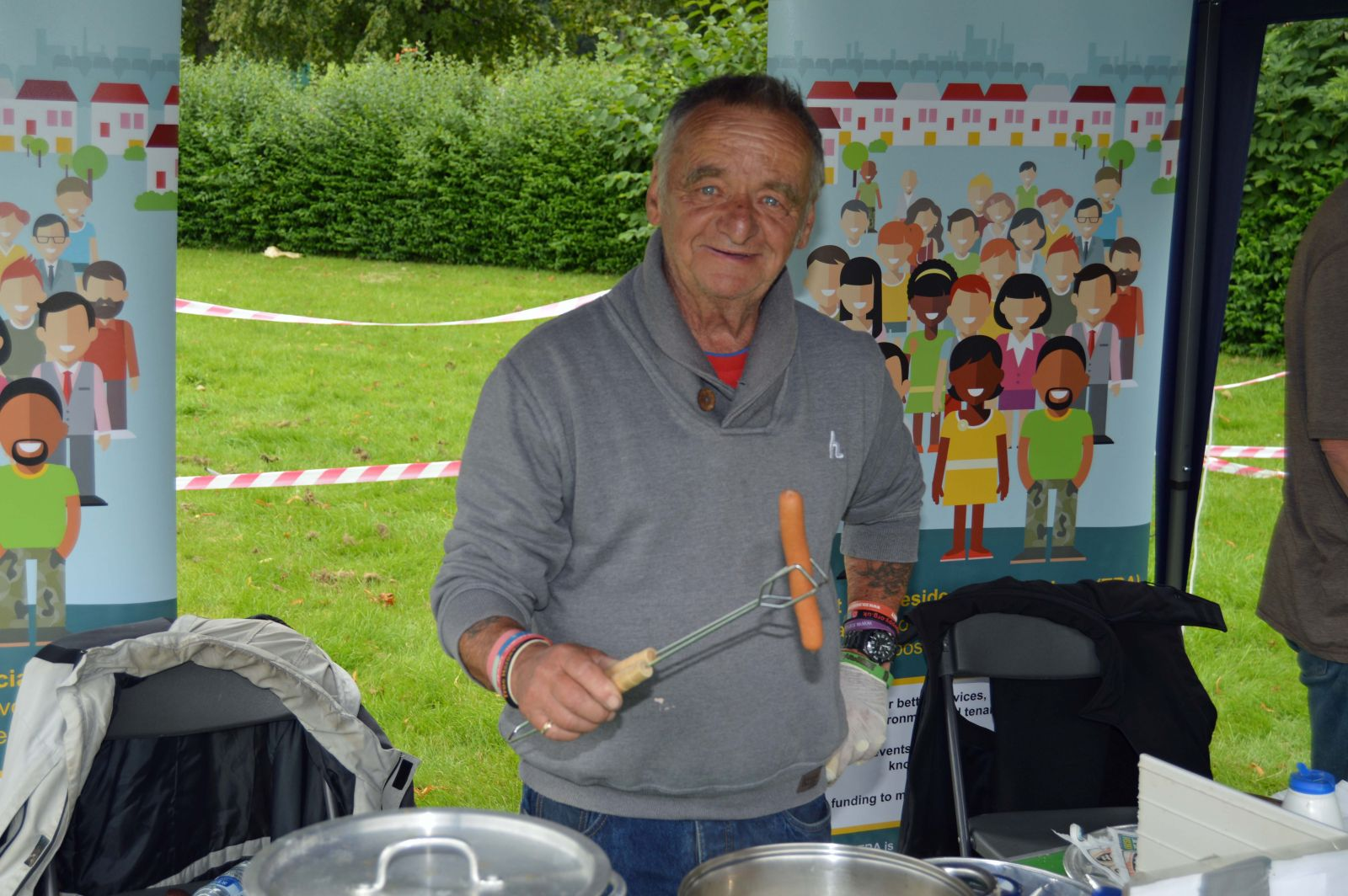 Chesham Fold TRA volunteer serves up hotdogs at Six Town Housing Summer Roadshow in Bury