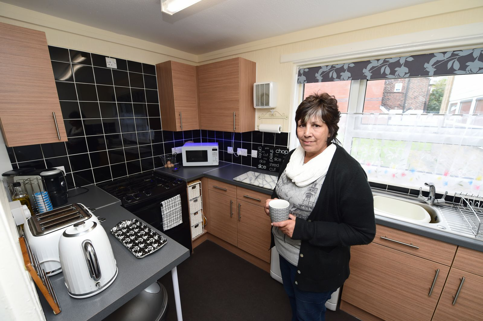 Six Town Housing tenant in a new kitchen following improvement works.