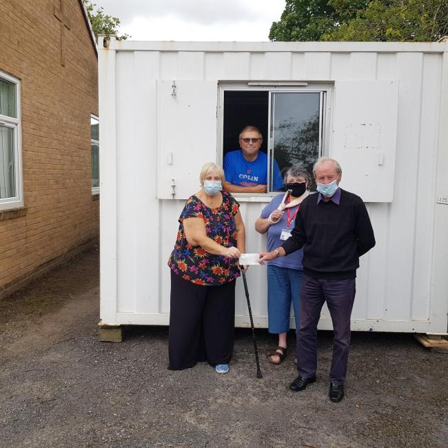Trinity Foodbank volunteers receiving a cheque from Gerry Faulkner, Treasurer of Radcliffe Rotary Club for the new cabin.