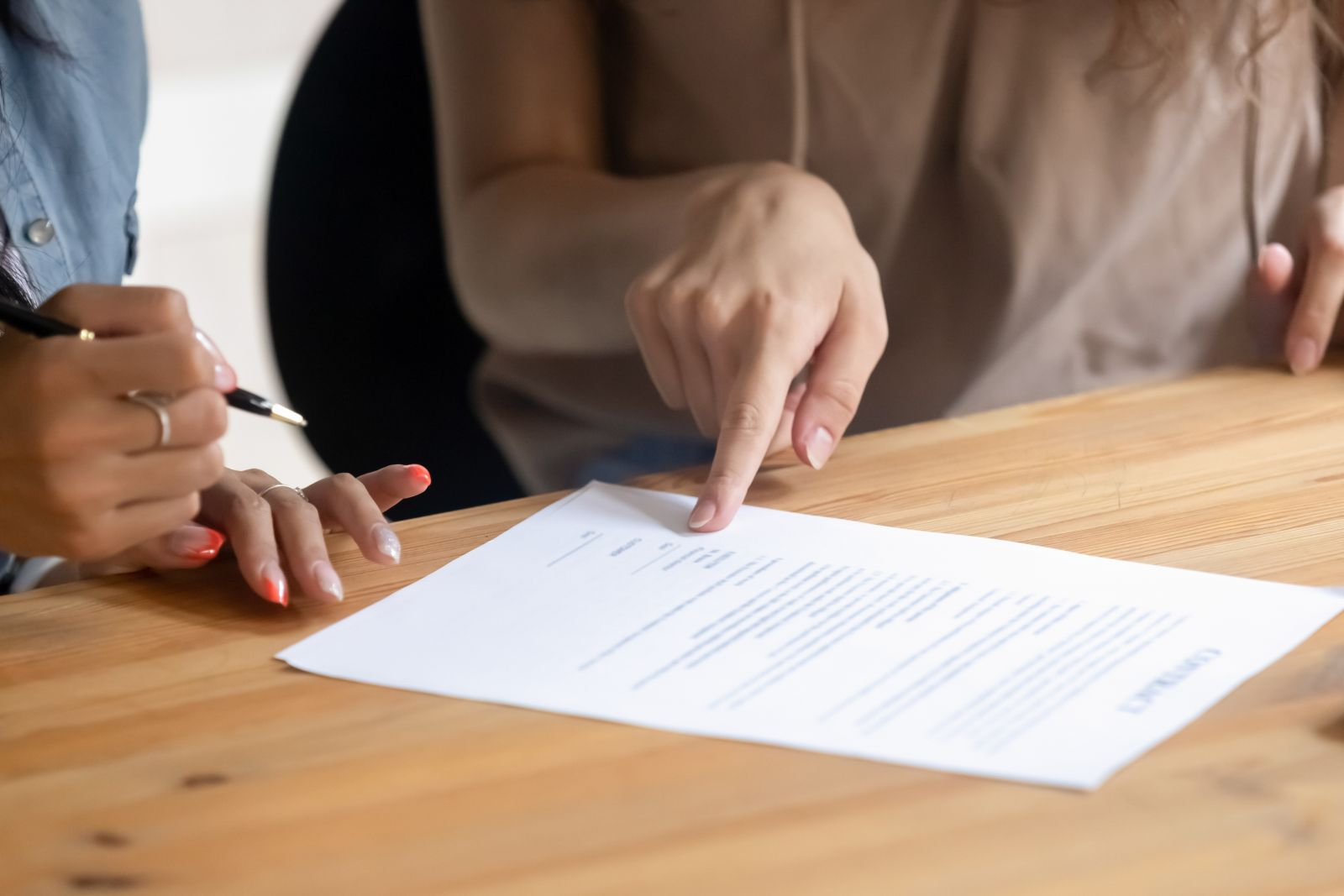 Close up view of client customer hand put signature on business contract, female lawyer solicitor pointing at paper showing where to sign document selling services making financial legal deal concept
